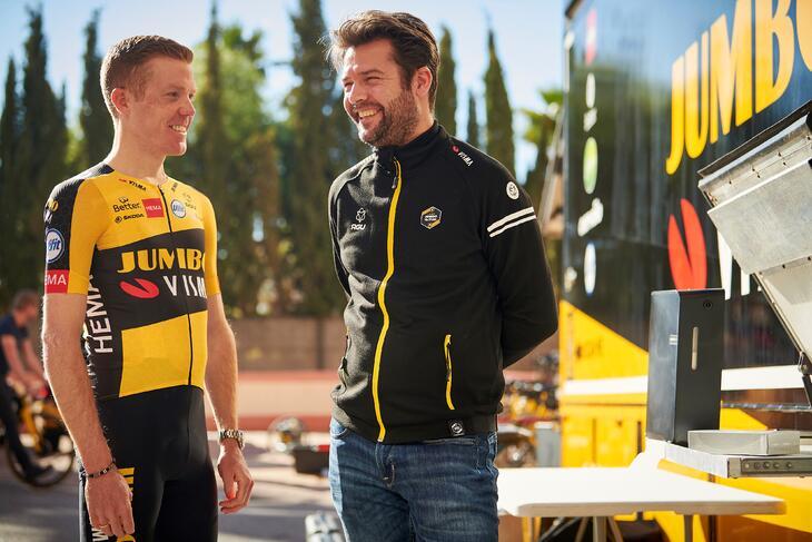 Team Jumbo Visma Sport Diretor Addy Engels smiling while standing beside a Team Jumbo Visma athlete.